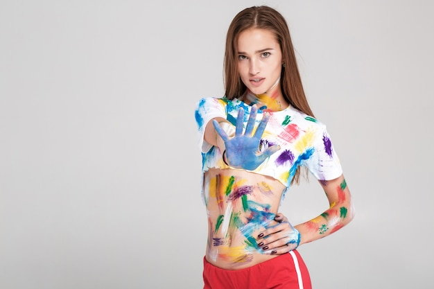 Женщина грязная в разноцветной краске. девушка показывает знак остановки. сосредоточиться на руке