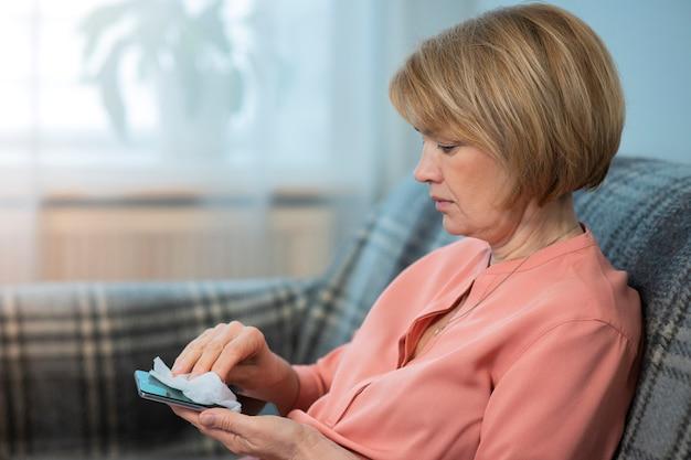 女性は自宅で携帯電話を消毒し、スマートフォンをナプキンで拭いて取り除く
