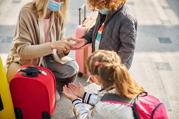 여자가 소독제로 아이들 손을 소독하고 있다