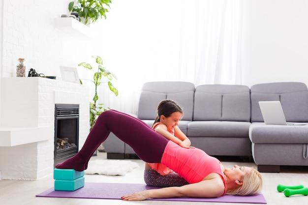 Женщина занимается онлайн-йогой с ноутбуком во время самоизоляции в своей гостиной, без тренировок с оборудованием, советы по медитации для начинающих. семейное время с детьми, оставайтесь дома.