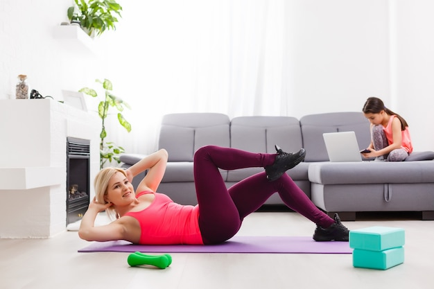 Woman is doing online yoga with laptop during self isolation at her living room, no equipment workout, meditation tips for beginners. her daughter is reading. family time with kids, stay home.
