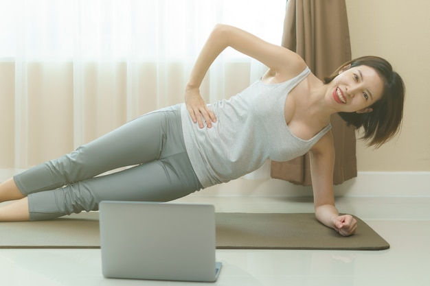 Woman is doing side plank exercises, looking at the laptop in the living room on floor mat at home.