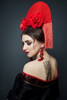 Женщина одета в красную китайскую японскую народную одежду. летящая ткань, красивый зонт и веер в японско-китайском стиле, длинные серьги в ушах. рисунок текста любовного стихотворения на китайском языке