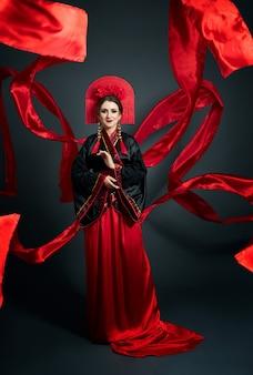 여자는 빨간 중국 일본 민속 의상을 입고 있습니다. 날아가는 천, 아름다운 우산과 일본 중국 스타일의 부채, 귀에 긴 귀걸이. 어두운 배경에서 포즈를 취하는 소녀