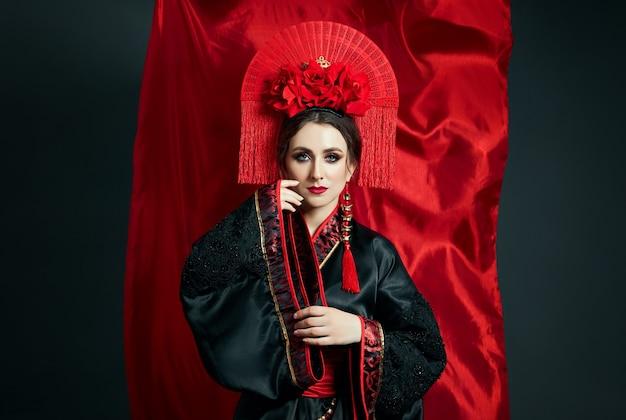 Женщина одета в красную китайскую японскую народную одежду. летящая ткань, красивый зонт и веер в японско-китайском стиле, длинные серьги в ушах. девушка позирует на темном фоне