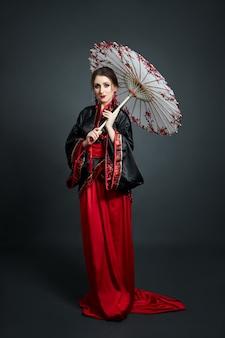 女性は赤い中国の日本の民俗服を着ています。フライングファブリック、和風の美しい傘と扇風機、耳に長いイヤリング。暗い背景でポーズをとる女の子