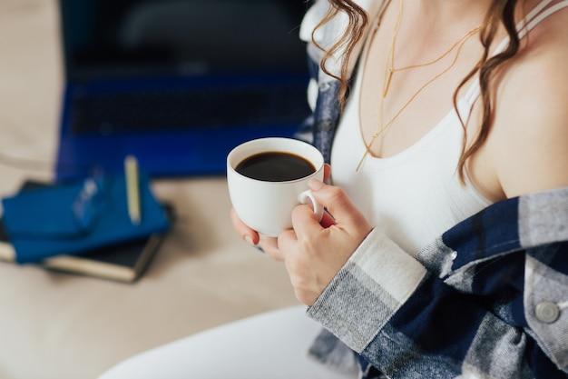 여자는 휴식 시간 동안 커피를 마시고있다