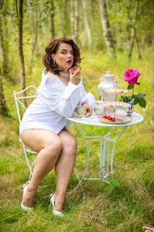 自然に朝の女性がコーヒーを飲んでいます。