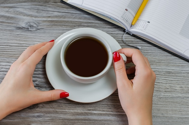Woman is drinking tea while having time off from writing and studying
