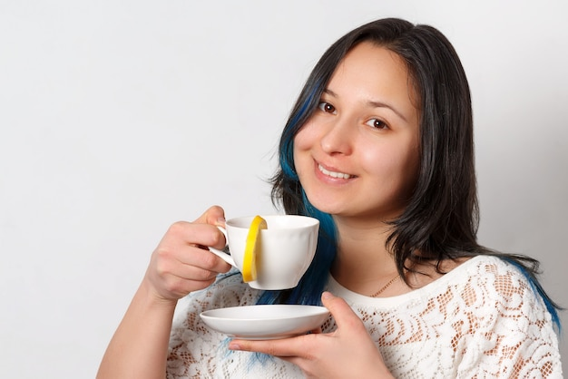 A woman is drinking tea with a lemon