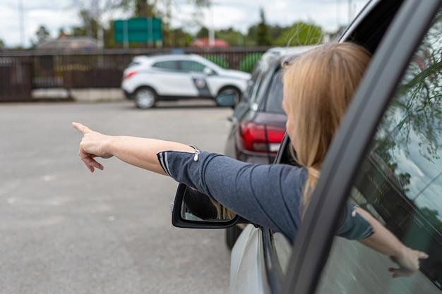 여자는 그녀의 차를 매우 공격적으로 운전하고 뒤에서 virw 그의 손 손가락으로 제스처를 제공합니다