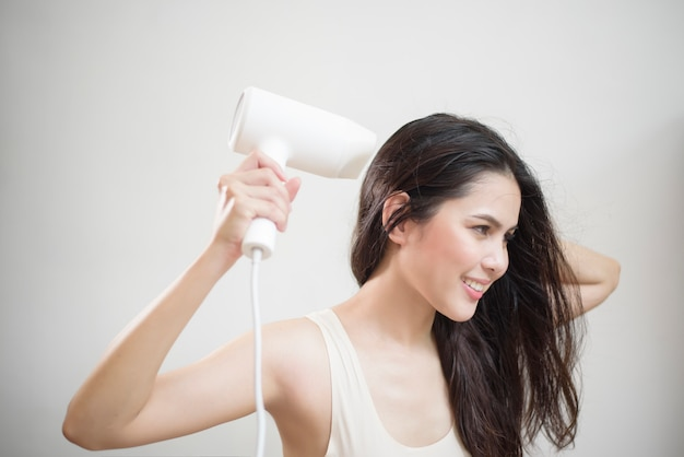 A woman is drying her hair after showering