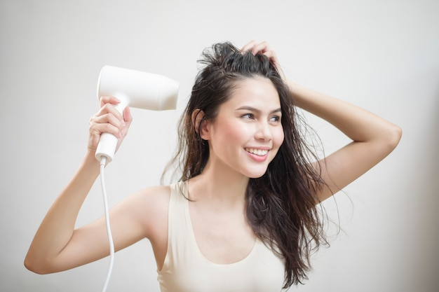 Woman is drying her hair after showering