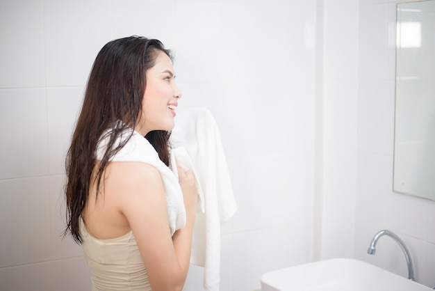 A woman is drying her hair with a towel after showering