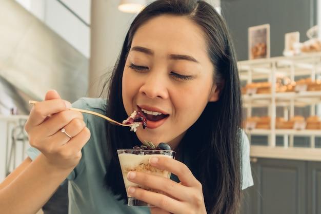 Женщина ест торт в кафе-пекарне.
