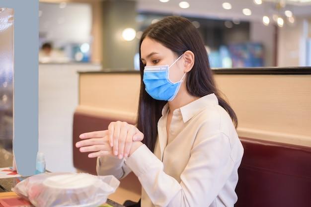 コロナウイルスのパンデミックにより市を封鎖している間、女性は社会的距離プロトコルでレストランで食事をしています