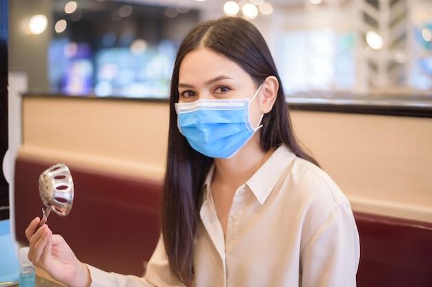 코로나 바이러스 전염병으로 인해 도시가 폐쇄되는 동안 사회적 거리를 둔 프로토콜로 식당에서 식사하는 여성 프리미엄 사진