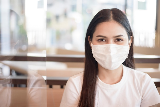 Woman is eating in restaurant with social distancing protocol while lockdown city due to  coronavirus pandemic