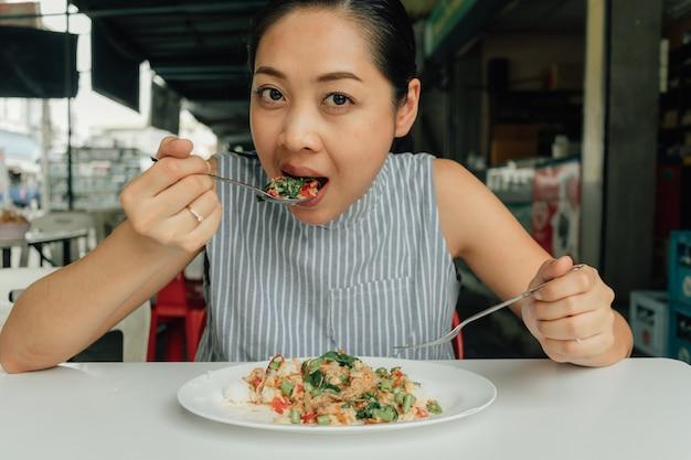 Woman is eating thai rice stir-fried pork and basil.