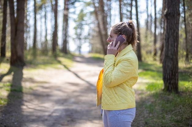 Женщина эмоционально разговаривает по телефону в лесу. концепция сотовой связи 5g
