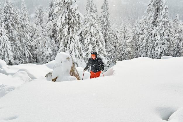 女性は降雪時に冬の山でトレッキングに従事しています