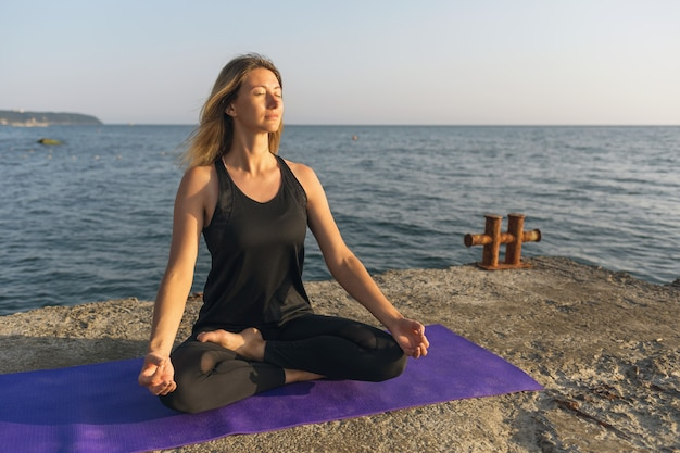 A woman is engaged in meditation, sits on a mat in a lotus position, on a sunny evening by the sea