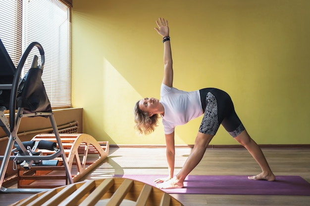 A woman is engaged in yoga in the studio, performs the triangle exercise, utthita trikonasana pose