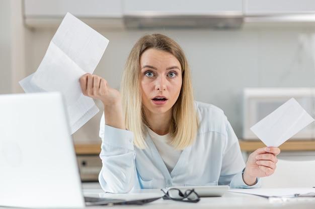 Женщина измучена и разочарована документами предприятия или семейного бюджета дома.