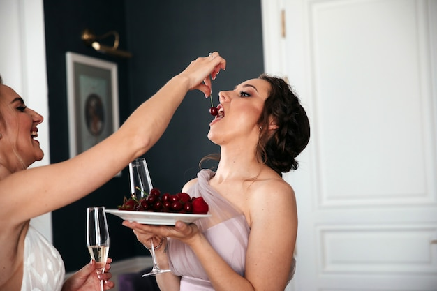 Woman is feeding another woman the cherry, they have fun