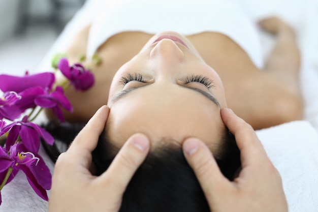 Woman is given facial massage at spa. beauty salon services concept