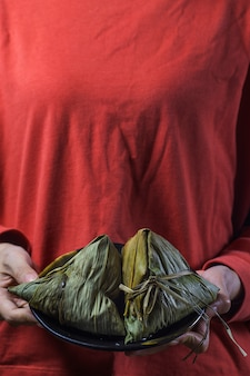 A woman is giving zongzi(rice dumpling) to others as a present on dragon boat festival,