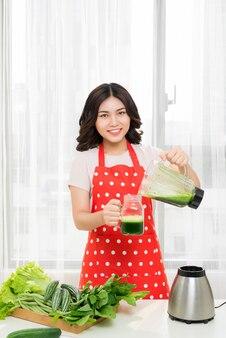 女性は朝食のためにブランダーで緑の健康的なシェイクに行きます