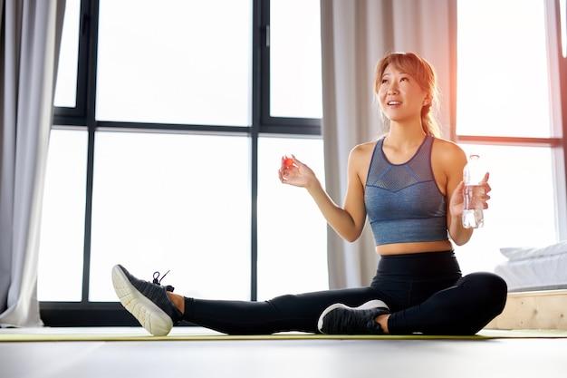女性は、マットの上に座って、スポーツ運動のトレーニングの後に水を飲むつもりです。健康的な生活様式