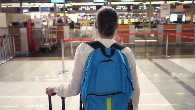 女性は空港ターミナルの背面図の登録デスクに行きます