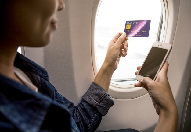 Woman is hand holds a credit card and a smartphone on the plane.
