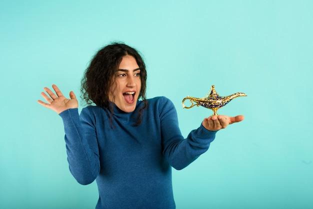 Женщина счастлива, потому что нашла лампу аладдина. голубой фон