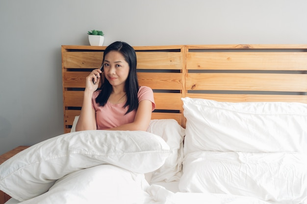 Woman is having a phone conversation on her bed in the morning.