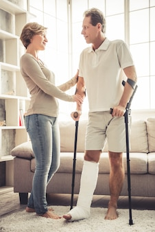 Woman is helping her handsome husband with broken leg.