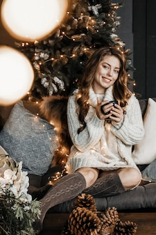 Женщина держит чашку кофе и улыбается.