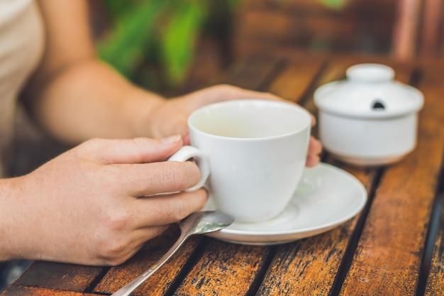 여자는 야외 카페에서 커피 한 잔을 들고있다