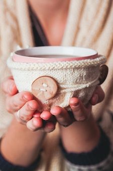 女性は熱いお茶を持っています