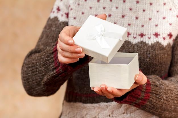 여자는 그녀의 손에 흰색 선물 상자를 들고 그것을 열고 있습니다. 필드의 얕은 깊이, 상자에 선택적 초점. 휴일이나 생일에 선물을 주는 개념.