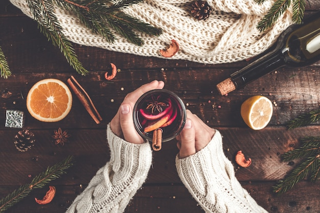 Woman is holding a christmas, hot mulled wine glass.