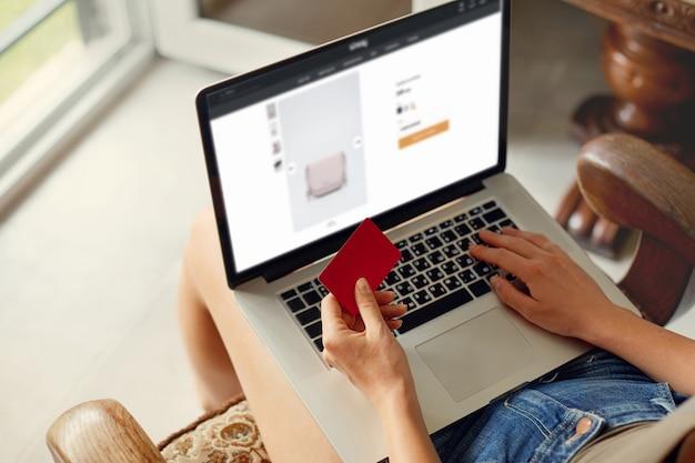 Женщина держит кредитную карту и использует портативный компьютер. концепция покупок интернет-технологий. работать из дома