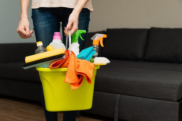 A woman is holding detergents in a bucket. woman is ready to clean house