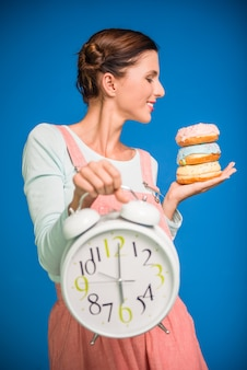 Woman is holding donuts and clock.