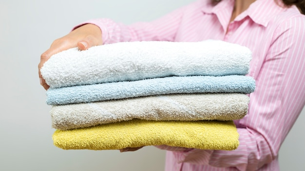 A woman is holding folded clean towels.