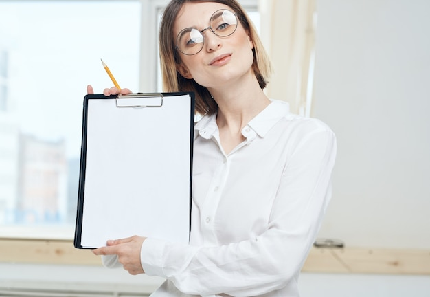 A woman is holding a folder with a white sheet of mockup paper