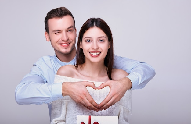 Woman is holding a gift box while guy is showing heart, both are smiling.