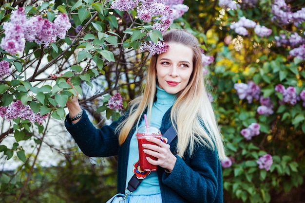 Woman is holding glass of vitamin smoothie in her hands by a floral tree